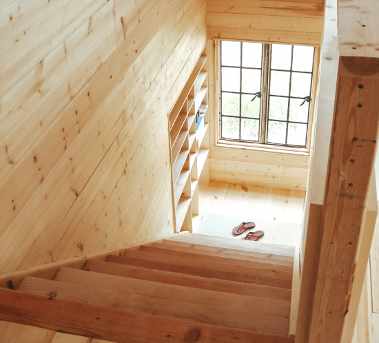 Rustic natural wood plank staircase with sandals at the bottom