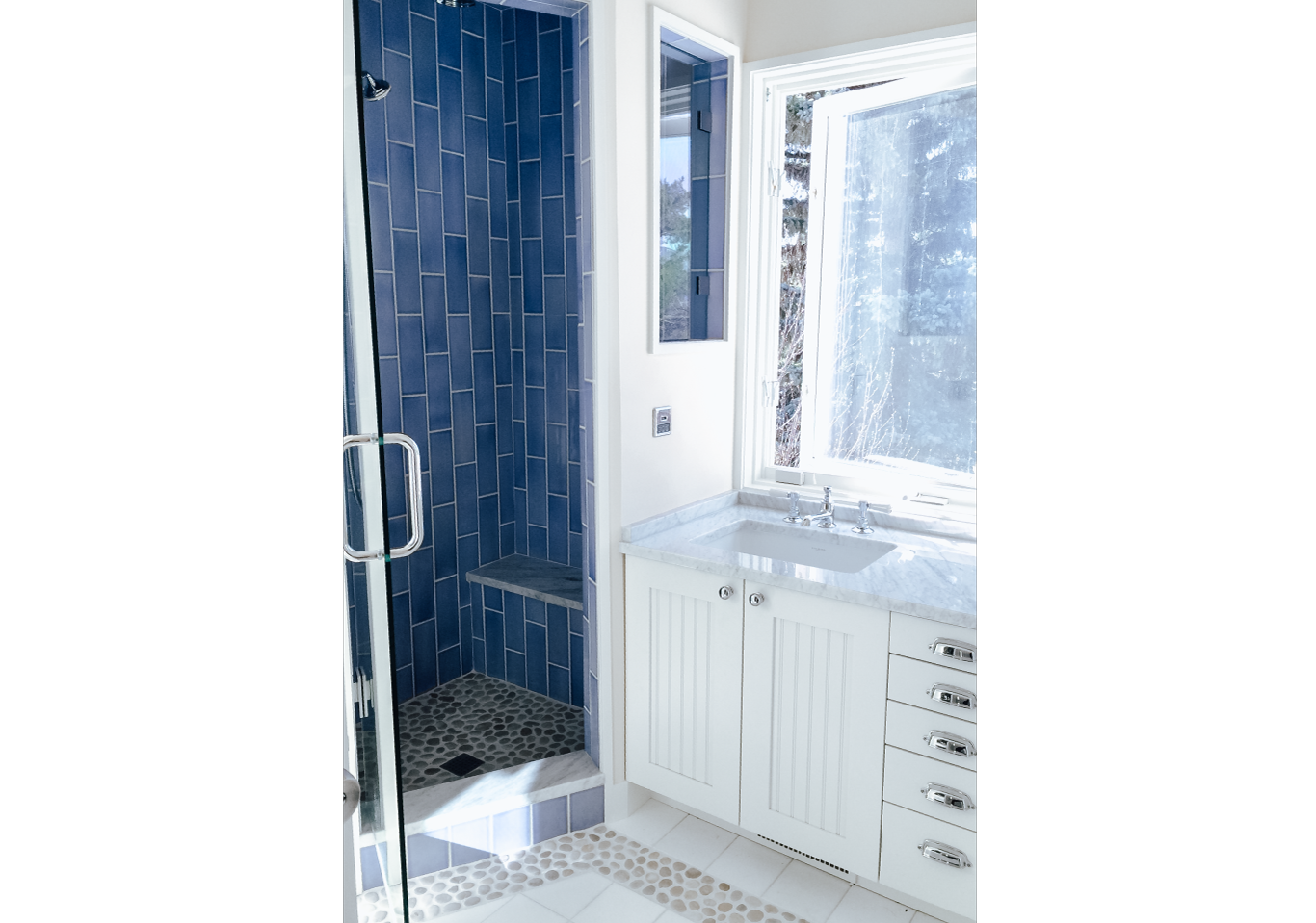 Blue vertical tiled shower next to white counter
