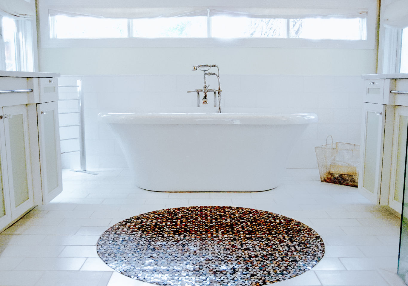 White porcelain bathtub and bathroom with brown circular floor mosaic