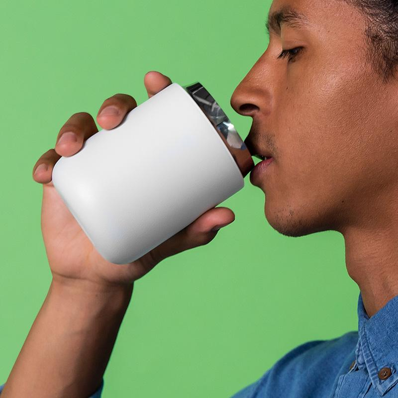 male drinking out of fellow mug on the go