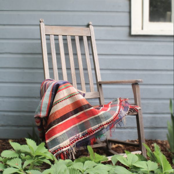 multi-colored throw blanket resting on rocking chair