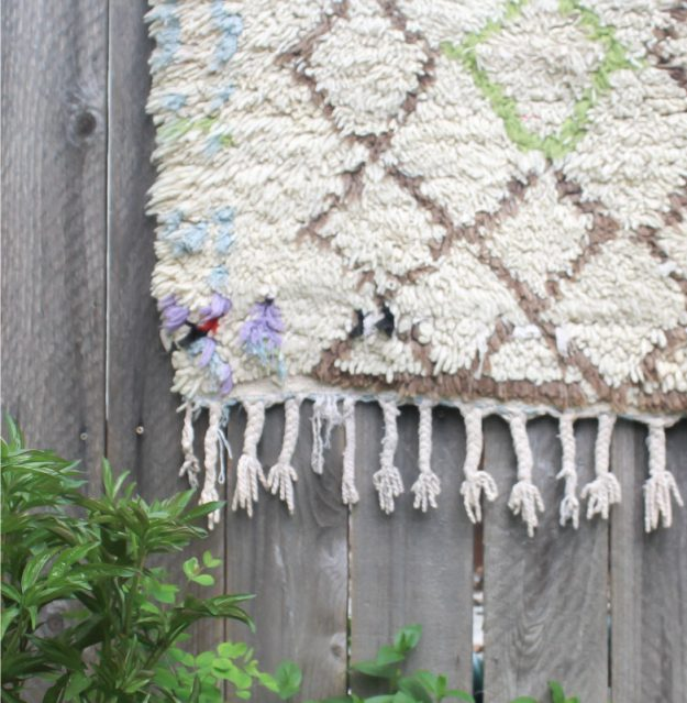 cream rug with tassels hanging over a wooden fence