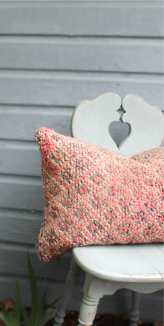 salmon colored pillow on a chair outside